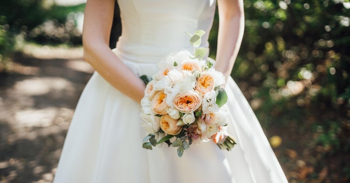 How Much it Really Costs to Throw a Traditional Wedding - cropped picture of bride holding bouquet