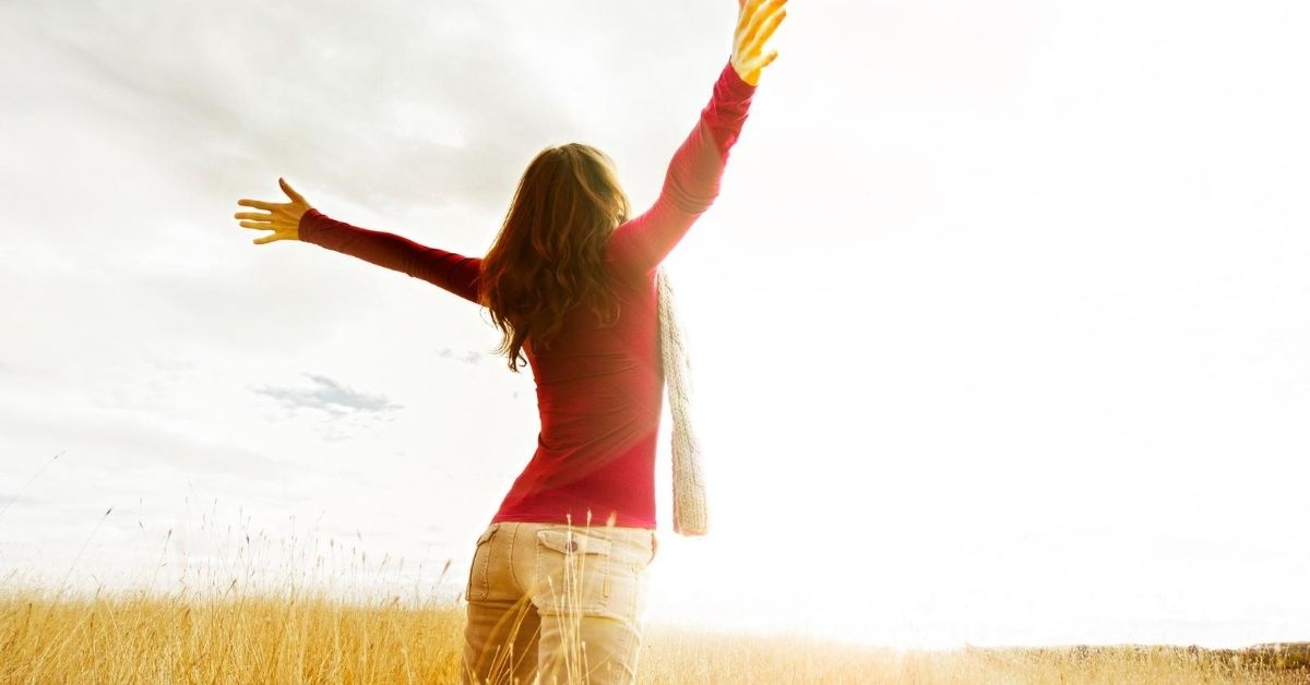The 5 Financial Habits that Changed My Life - picture of woman with outstretched arms in field