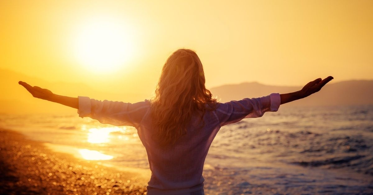 Why I Quit My Job - picture of back of woman at beach at sunset with outstretched arms