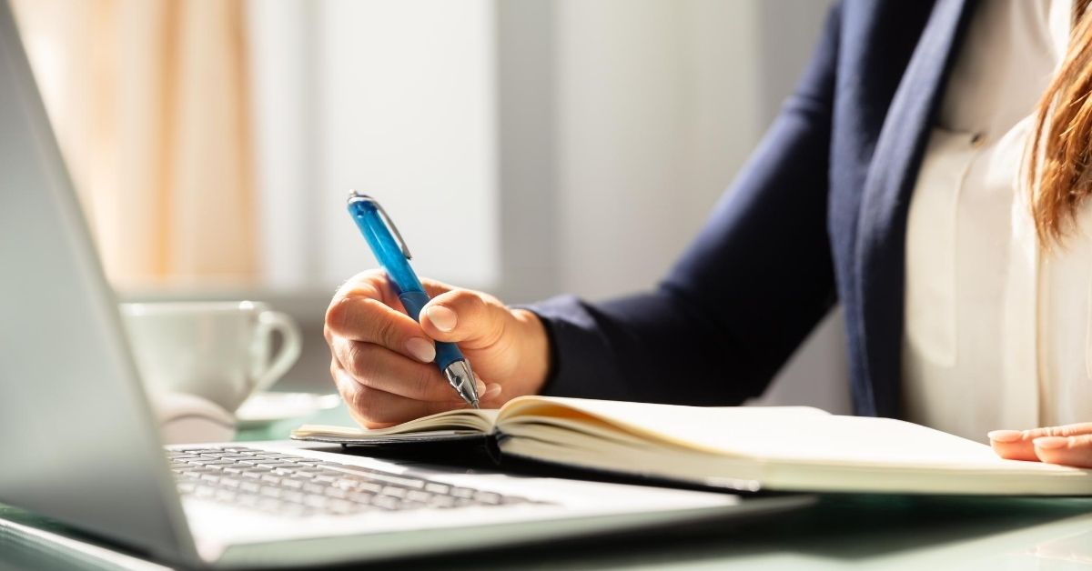 Cash Money 6,605 in August Income and Blog Updates - picture of woman's hand writing in notebook propped up on laptop