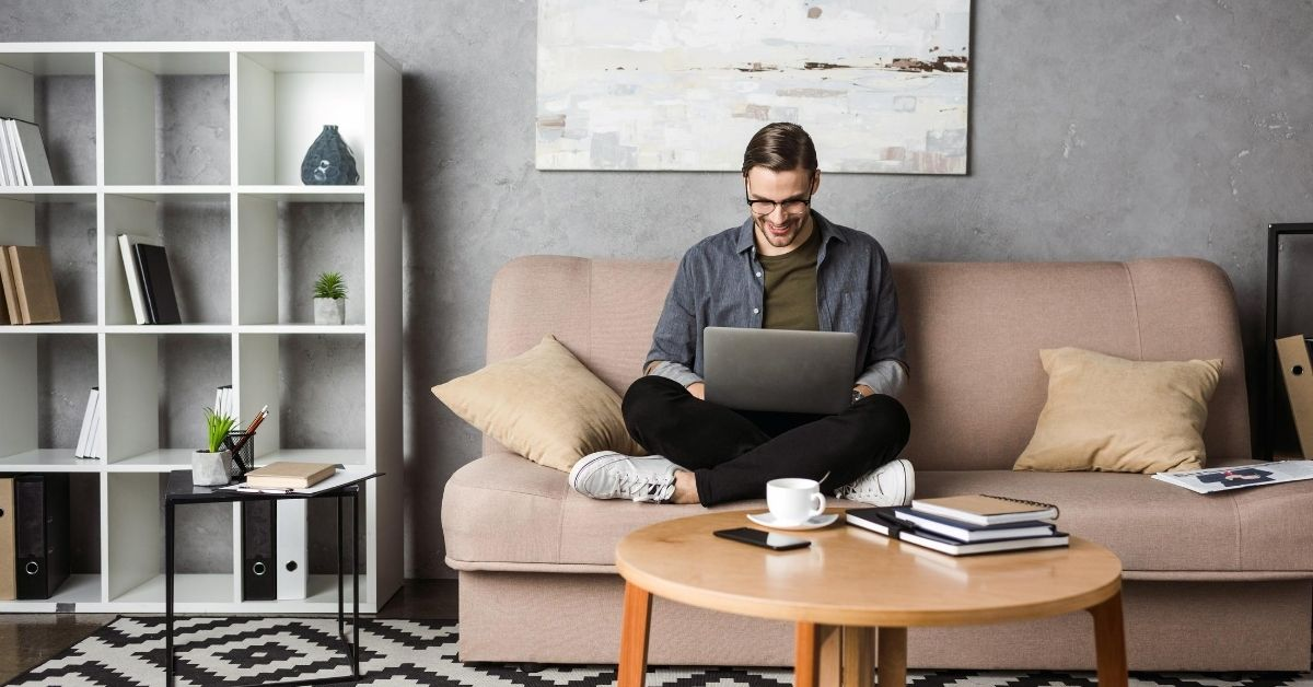Preparing Your Finances for a Freelance Career - picture of man sitting on couch with laptop in lap