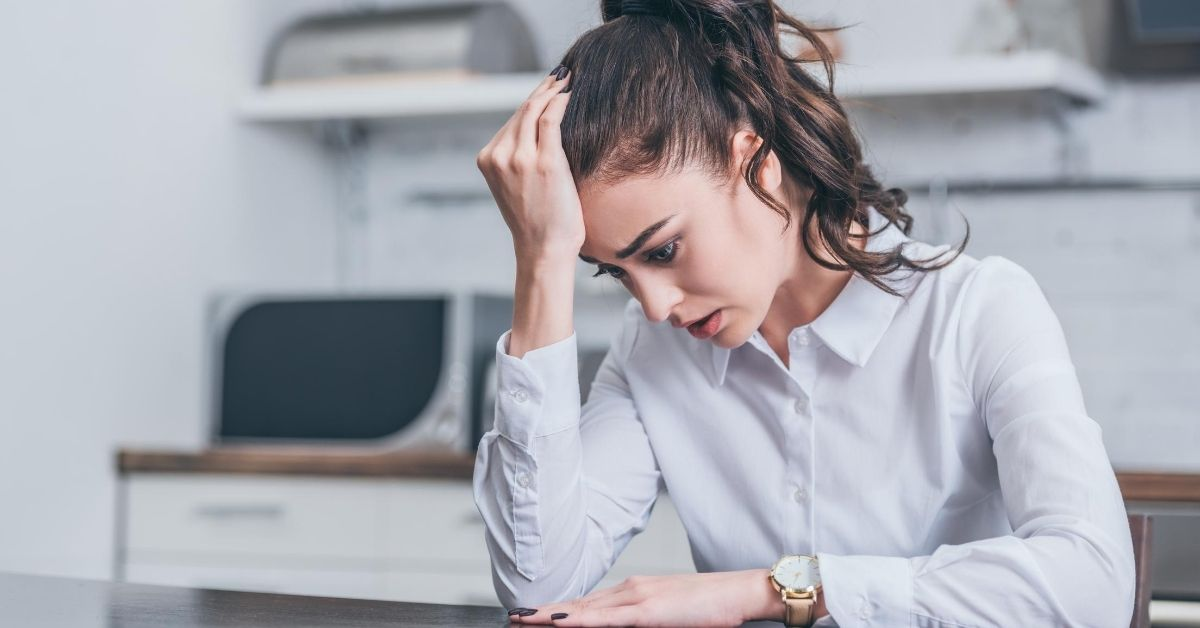 Being Unemployed Sucks - picture of woman with head in her hand looking sad
