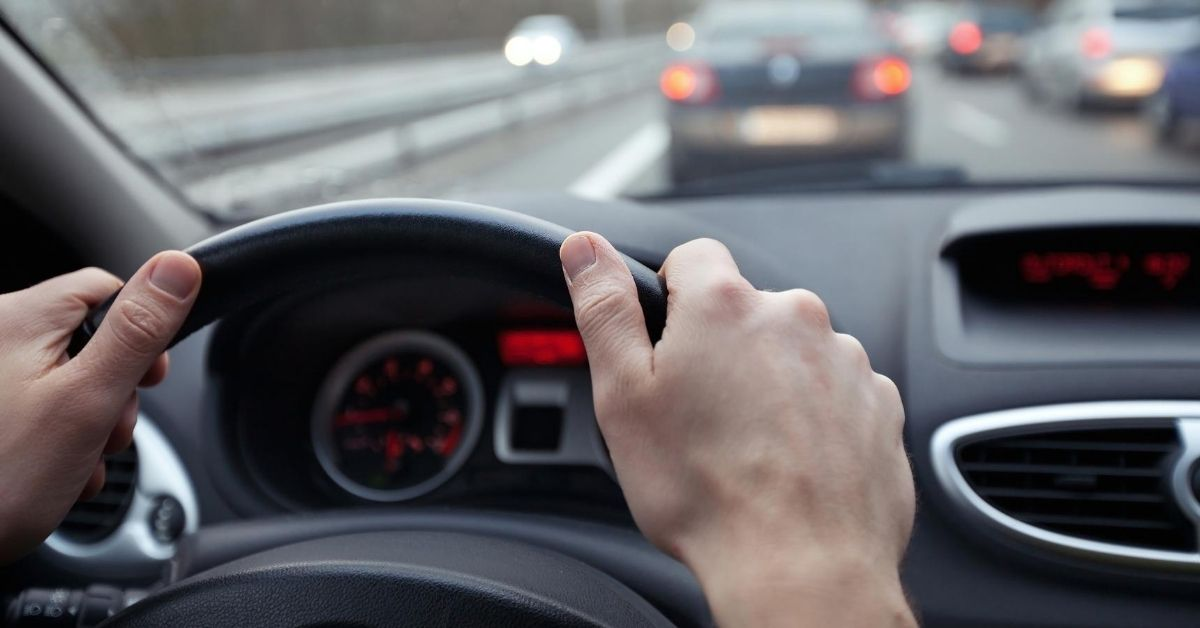 The High Cost of Commuting - picture of hands on steering wheel in traffic