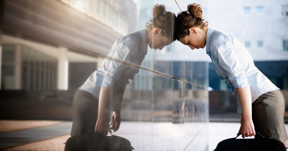 Thoughts on Working Hard - picture of sad businesswoman with head leaning against office building