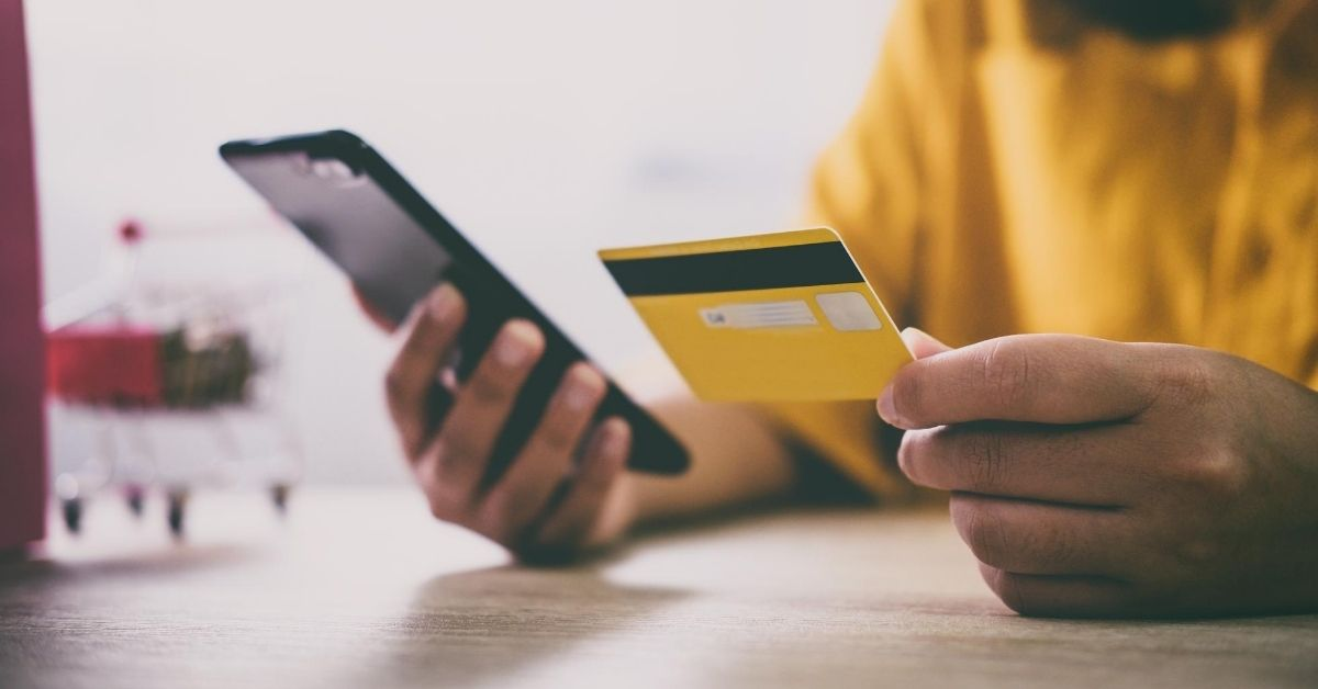 Does Pursuing Credit Card Rewards Hurt Your Credit Score - picture of hands holding credit card and cellphone