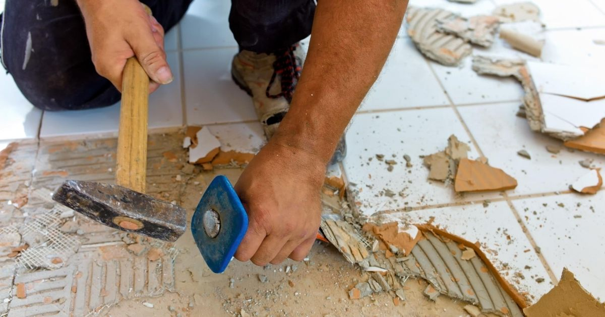 January Budget Breakdown and Home Remodeling Fun - picture of hands hammering up tile