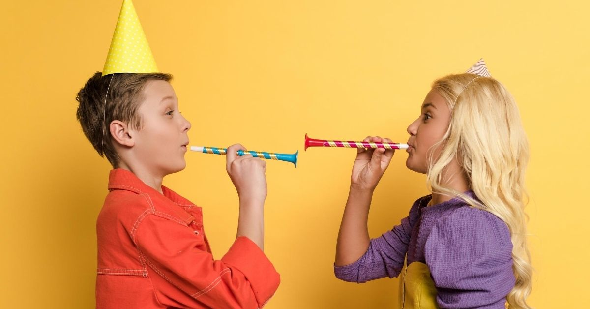 Joint Birthday Parties - picture of girl and boy in birthday hats blowing horns at each other