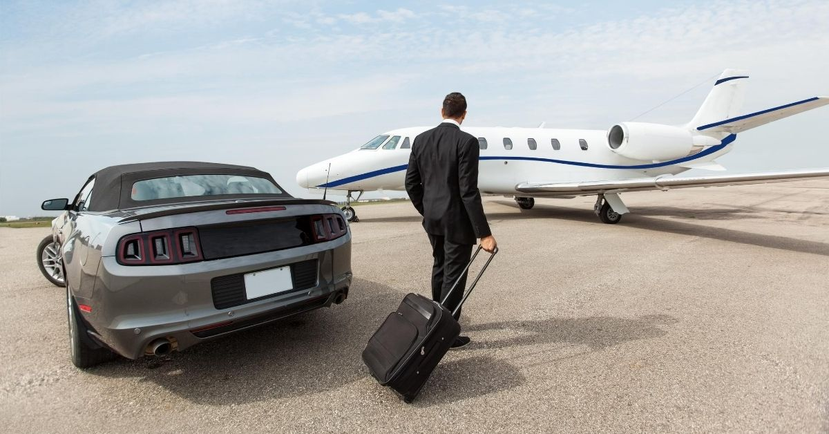 Park Avenue and the One Percent - picture of man with luggage walking from expensive sportscar to private jet