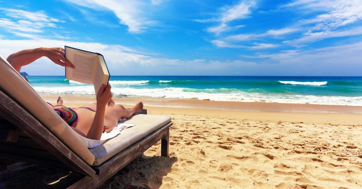 Reward yourself for good spending habits - picture of person reading on beach lounge