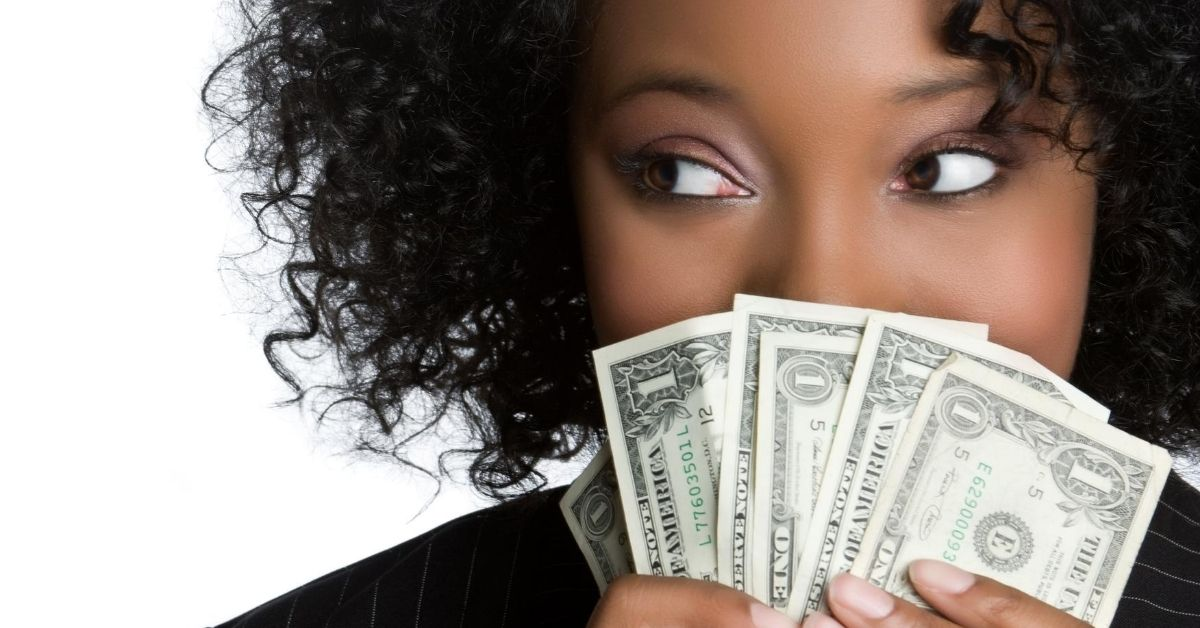 Embarrassing Ways to Save Money - picture of Black woman holding fan of dollar bills hiding part of her face looking to side