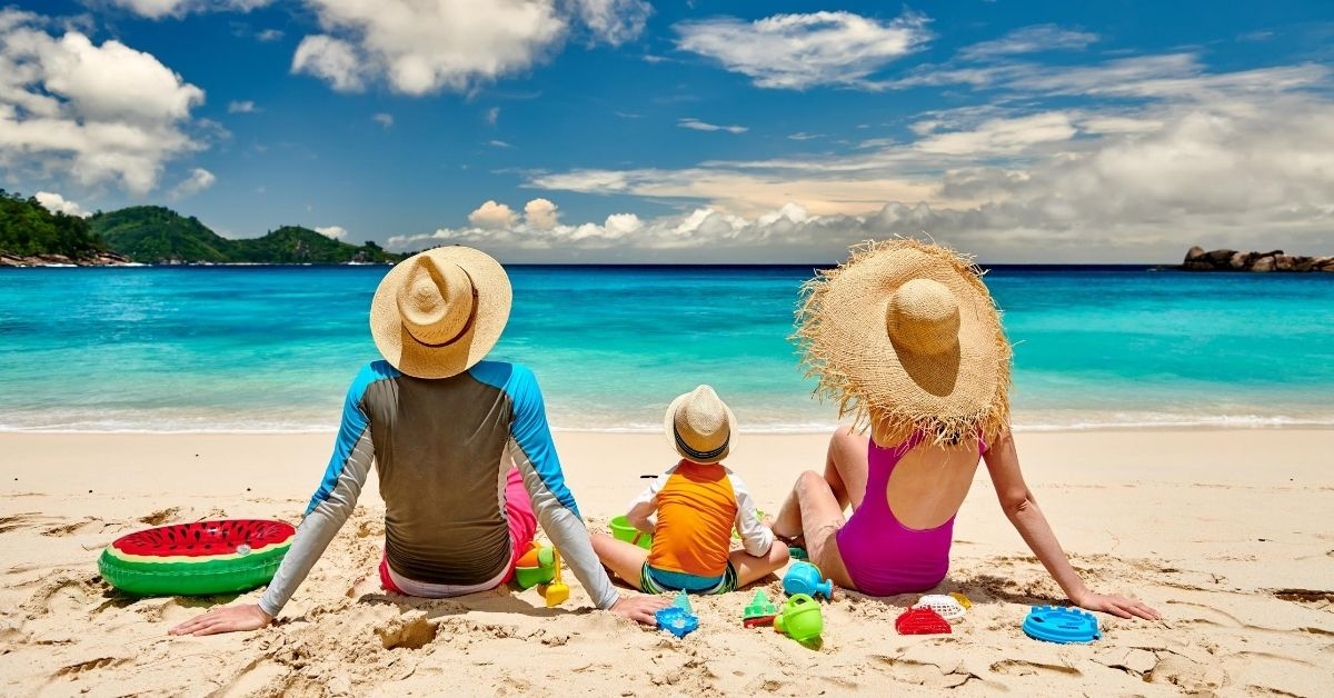 Saving for the Perfect Vacation - picture of parents and child between them sitting on beach looking out over ocean