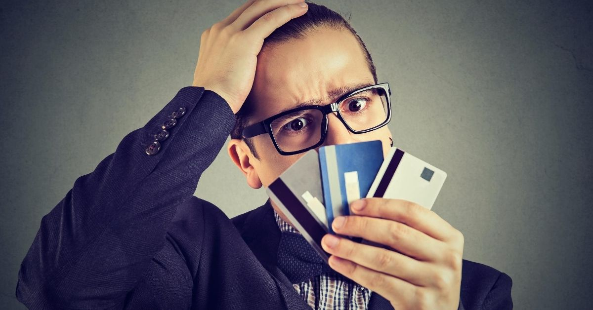 Vanilla Reloads Are Dead - picture of man holding fan of credit cards in front of his face with curious look
