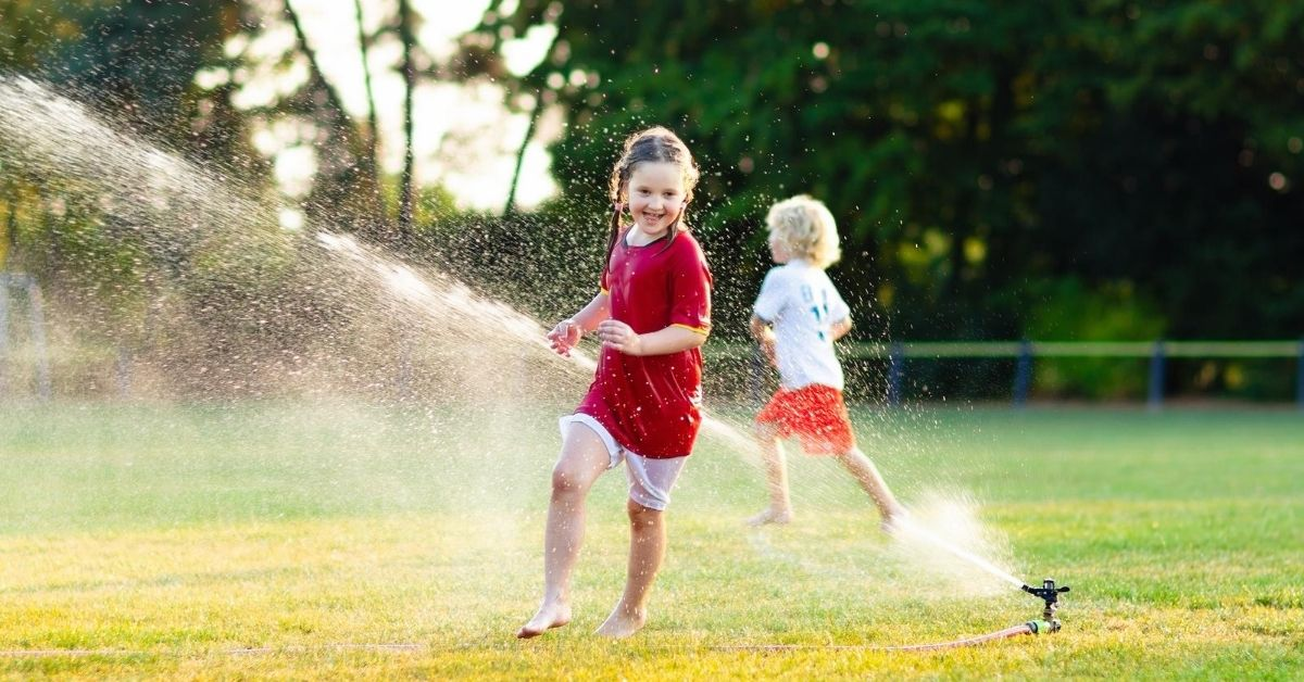 Cash Money $5,370 in May Income and Life Updates - picture of kids playing in sprinklers