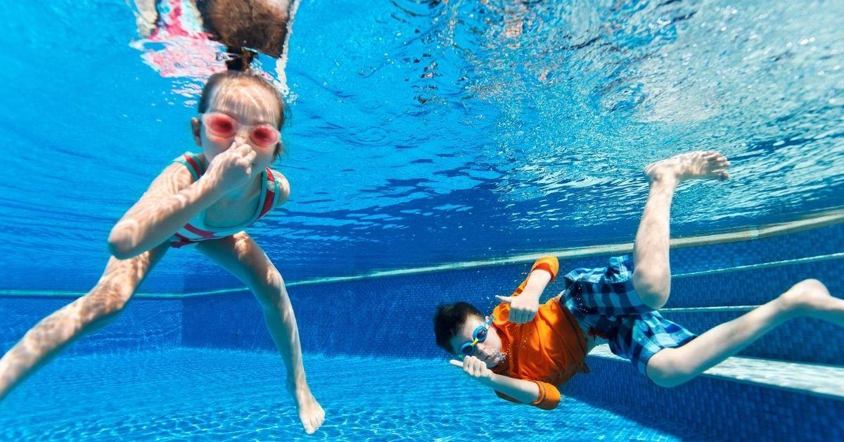 Fun Ways We're Saving Money This Summer - picture of kids swimming in pool underwater