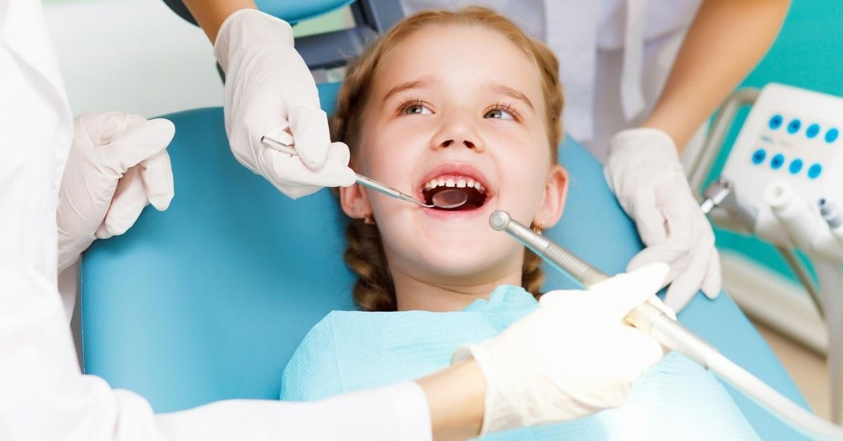 How to Combat the Crazy Cost of Dental Care - picture of little girl in dentist chair