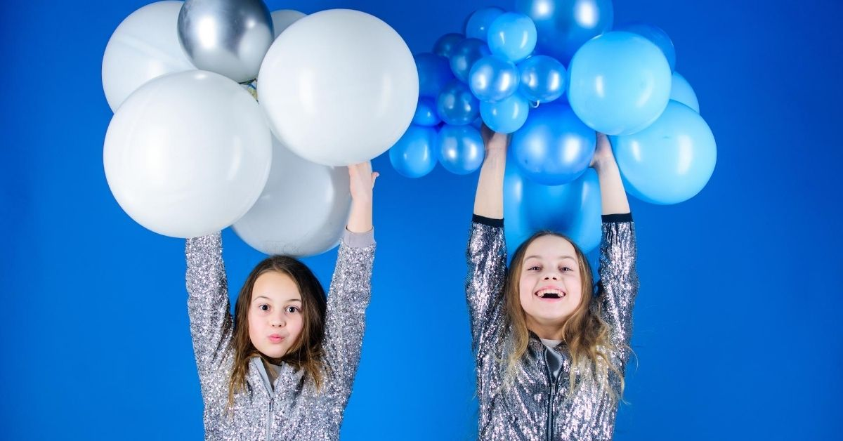 Joint Birthday Parties2 - picture of two girls holding up bunches of balloons