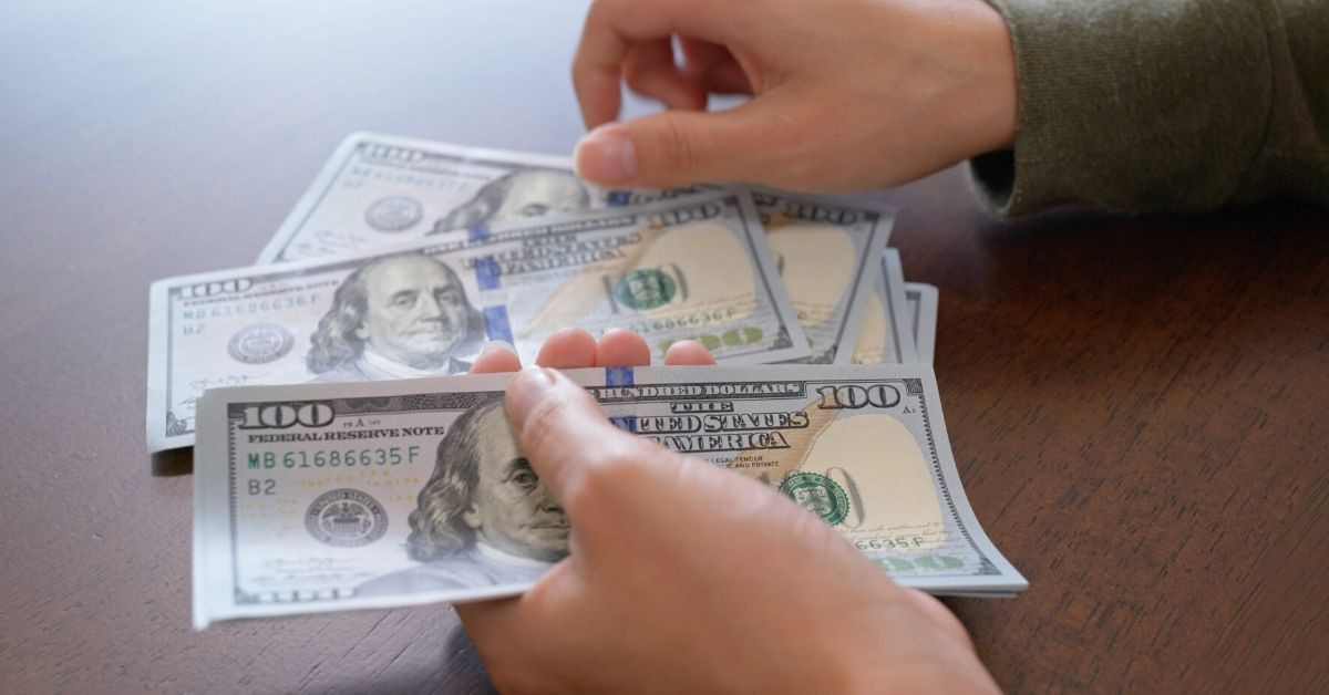 Cash Money $5,615 in June Income and Blog Updates - picture of hands counting hundred dollar bills