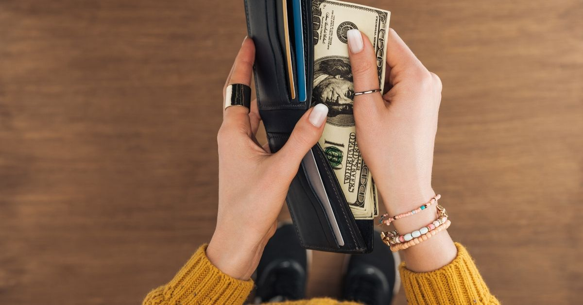 Do You Feel Comfortable Sharing Your Income - picture of top view of woman pulling cash out of wallet