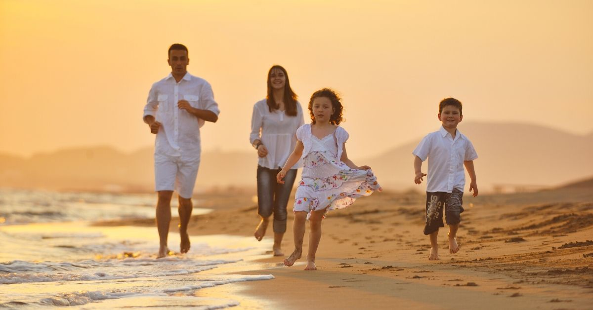 Turn Your Dream Vacation Into a Reality - picture of family running on beach at sunset