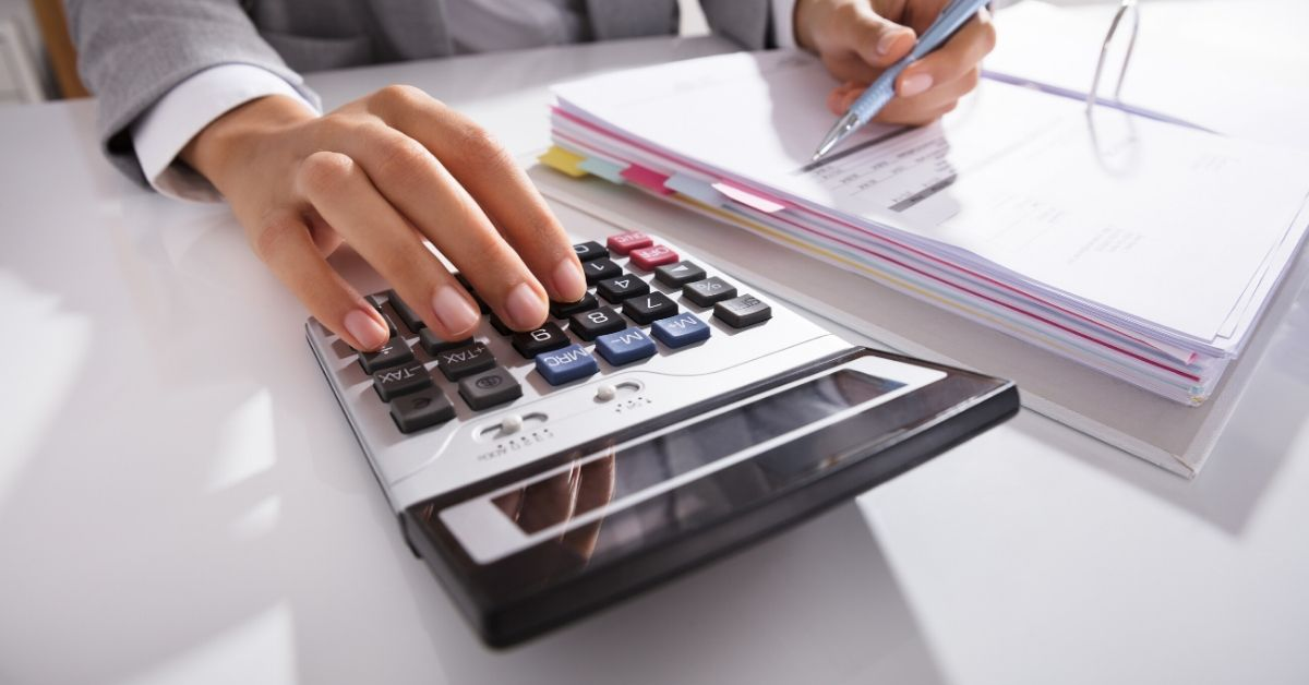 Club Thrifty August Budget Breakdown - close up picture of man's hands on calculator with pen and notebook