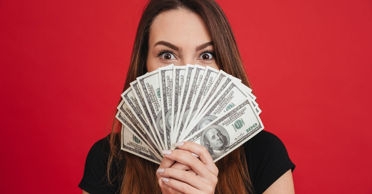 Those Awkward Money Moments - picture of woman with surprised look holding fanned out bills in front of her face