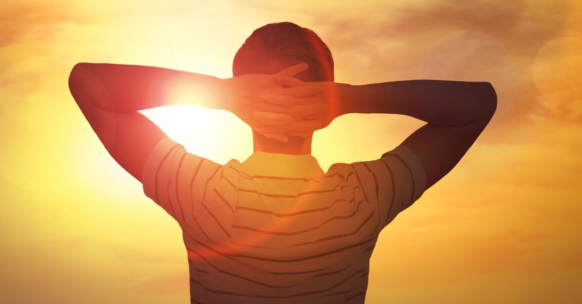 How to Get Anything You Want in Life - picture of silhouette of man at sunset with hands behind his head
