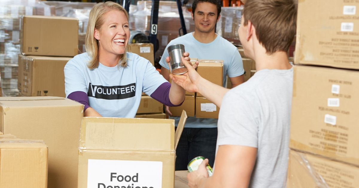 What Do Food Pantries Need - picture of volunteer accepting canned goods