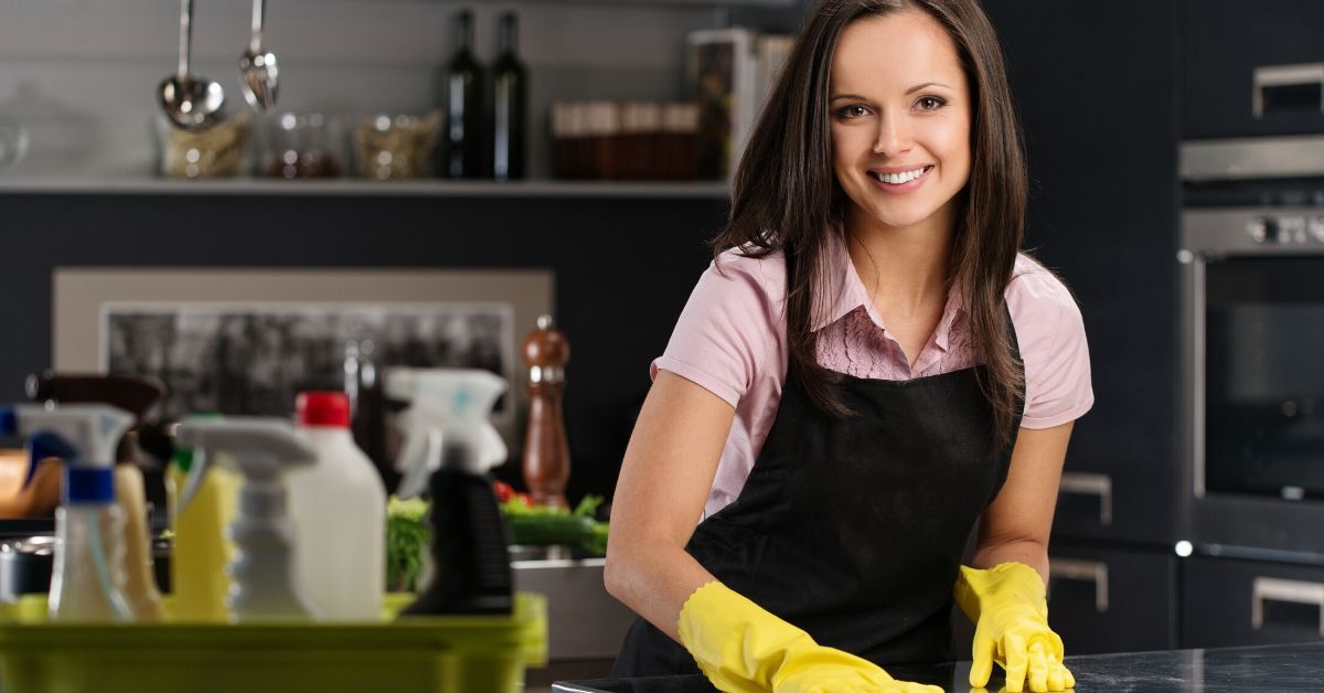Confession I Paid Someone to Clean My House - picture of woman cleaning a kitchen