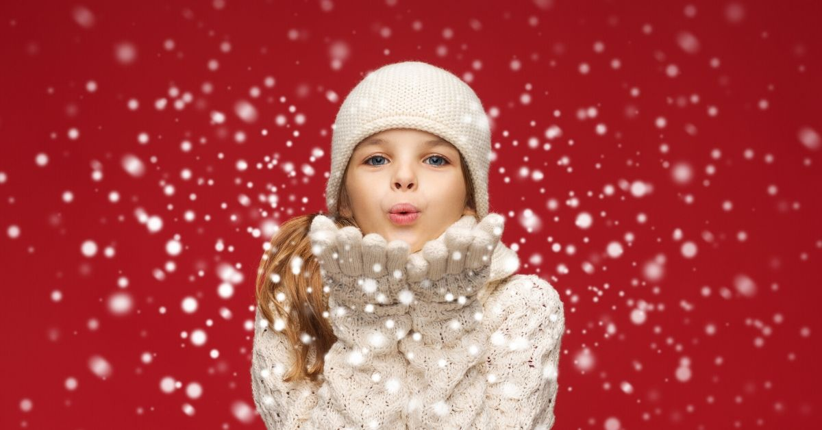 Holiday Money Lessons for Kids - picture of girl in white winter clothes blowing snow at camera