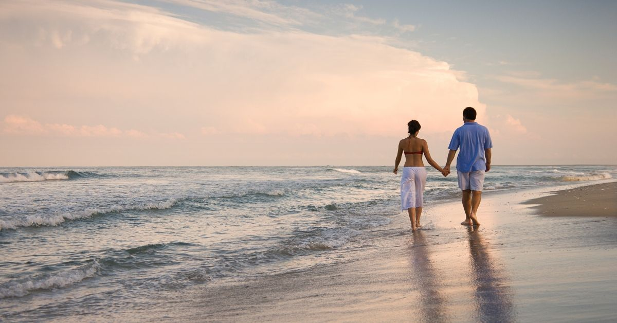 Confession I Have No Idea When We'll Be Able to Retire - picture of back of a couple walking down beach holding hands