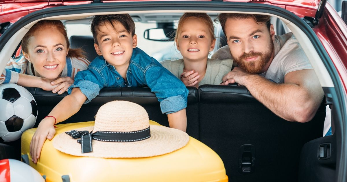 How to Travel with Kids On a Budget - picture of family in car with luggage