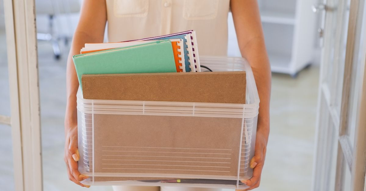 What Should You Do if You're Laid Off - picture of woman carrying box of office supplies