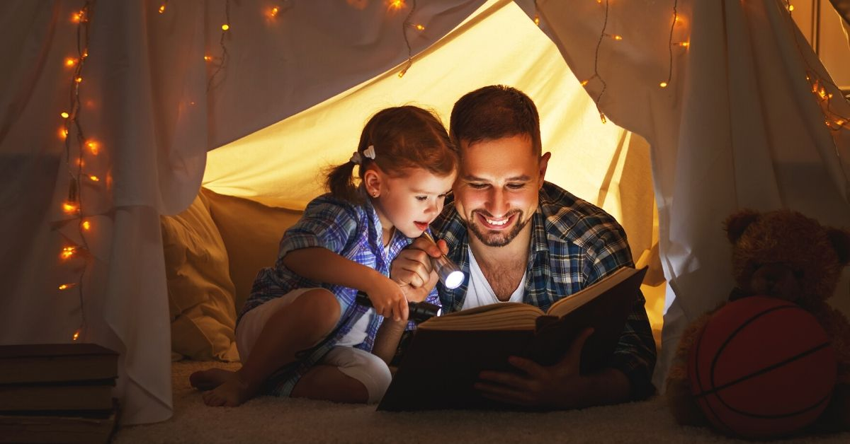 Frugal Parenting is Not Giving a Damn What Other People Think - picture of dad reading to young girl in a bedroom tent with lights