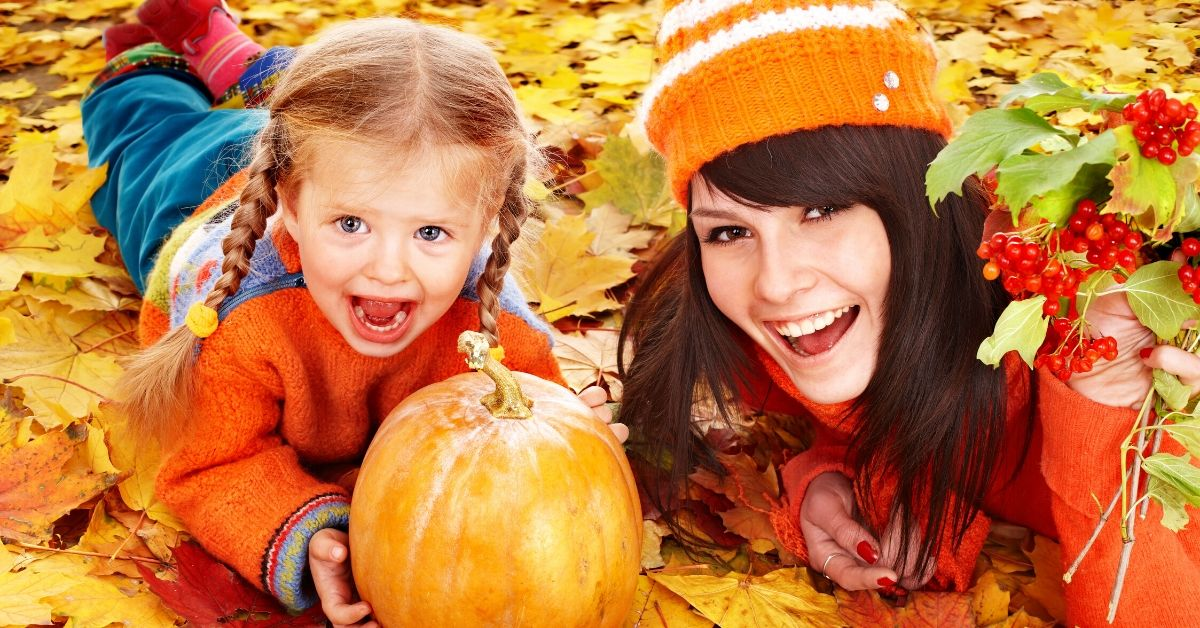 Brace Yourselves the Holidays are Coming - picture of mom and daughter with pumpkin in colorful fall leaves
