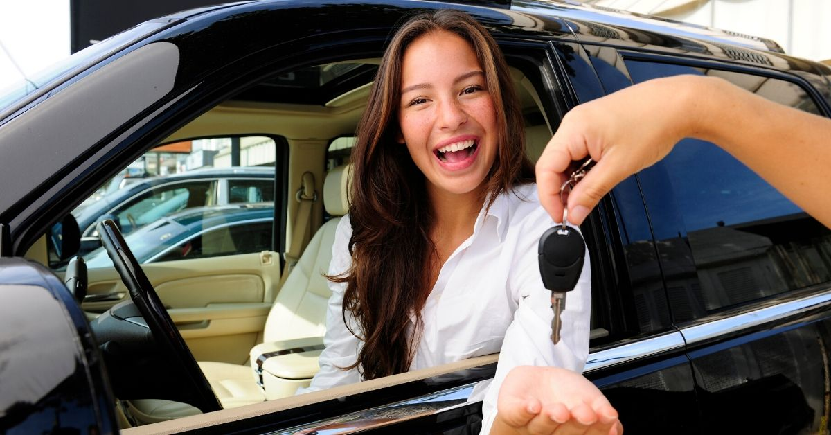 How to Buy a Used Car Like a Boss - picture of happy woman in car being handed keys