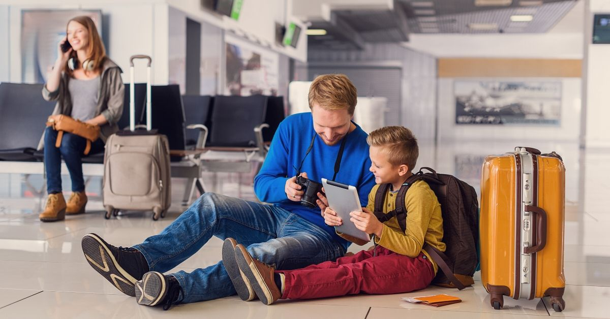 Tips for Saving Money at the Airport - picture of family in airport lounge playing games