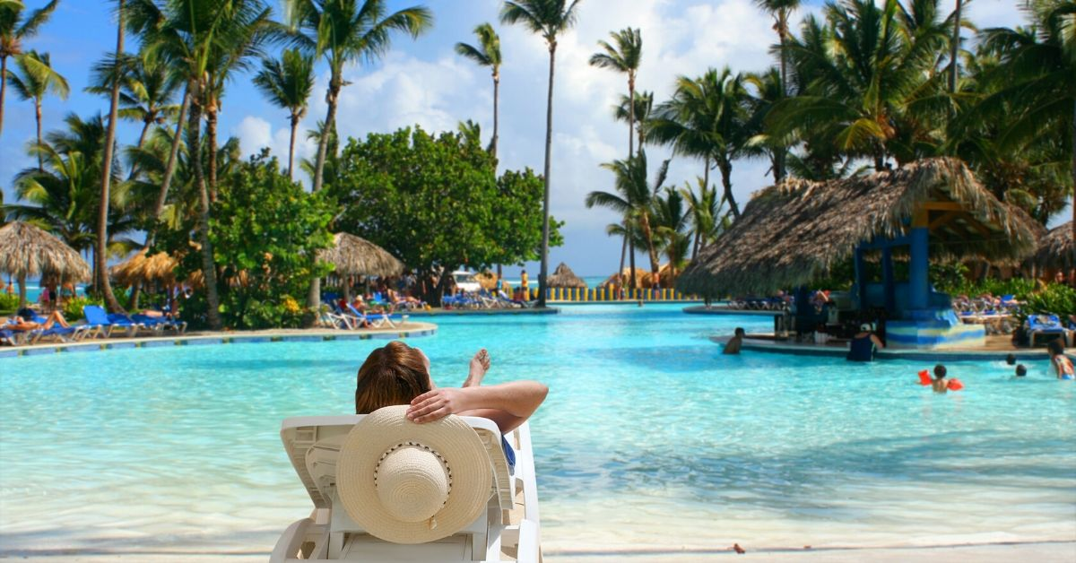 Why I'm Retiring at an All-Inclusive Resort - picture of woman sitting in lounge chair at tropical pool
