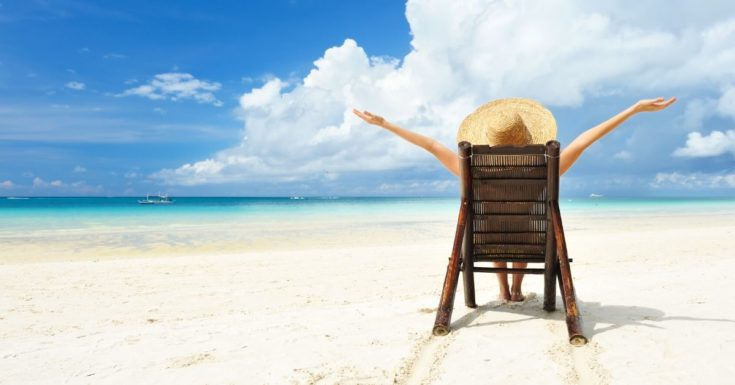 The 14 Best Gifts for Travelers - picture of back of woman sitting in beach chair with arms out