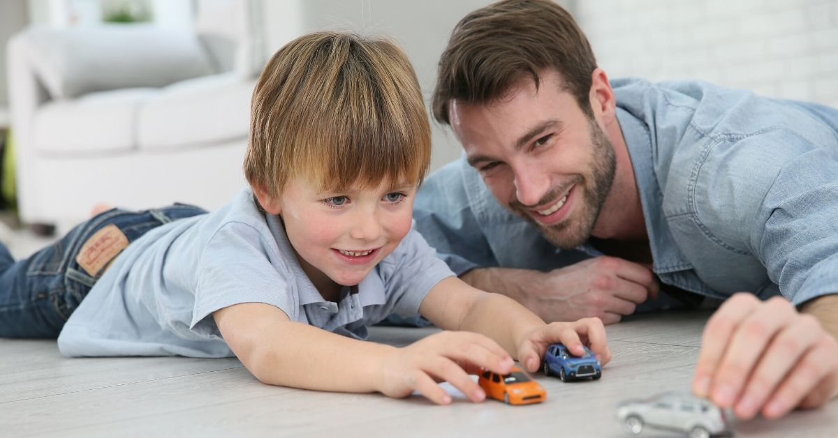 How I Save Money During My Wife's Solo Holidays - picture of father playing cars with son