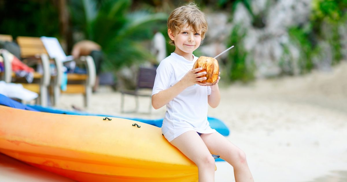 Saving Money on Family Travel with IBEROSTAR - picture of young boy sipping tropical drink on kayak at beach