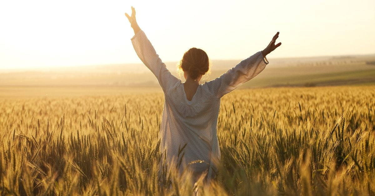 Simple Strategies to Destroy Debt Fast_picture of woman with arms raised in a wheat field