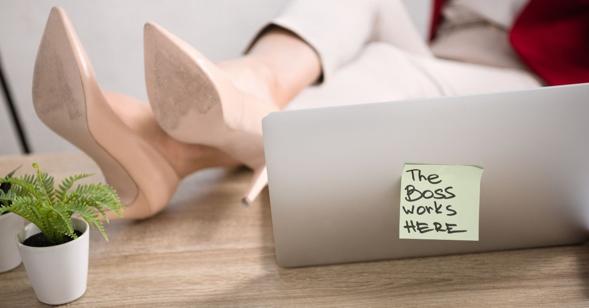 How to Track Your Spending Like a Boss - picture of women's feet in heels on desk with laptop
