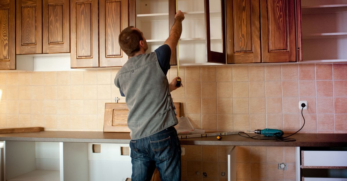 We Went $3,000 Over On Home Remodel - picture of man measuring kitchen cabinets