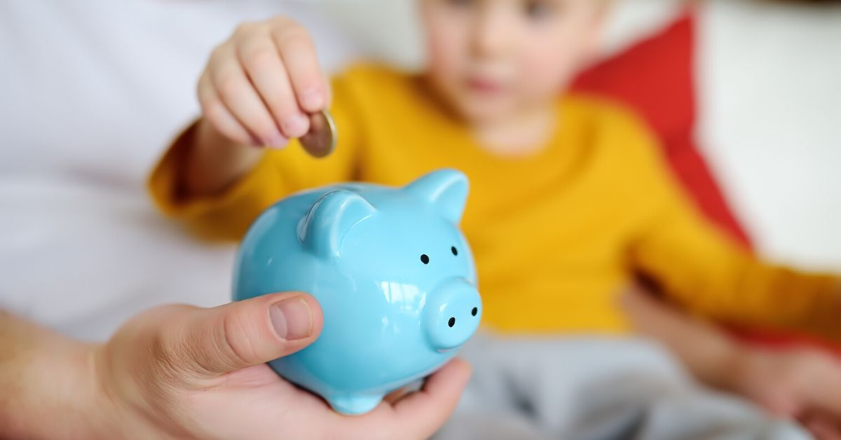 What I've Learned About Money by Becoming a Parent - picture of young boy putting coin in blue piggy bank