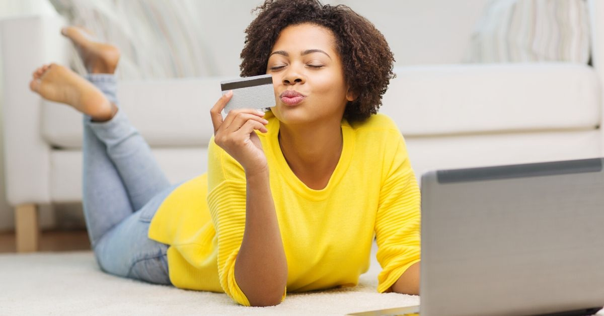 Favorite Credit Cards for Everyday Spending - picture of African American woman kissing credit card with laptop on floor in front of her