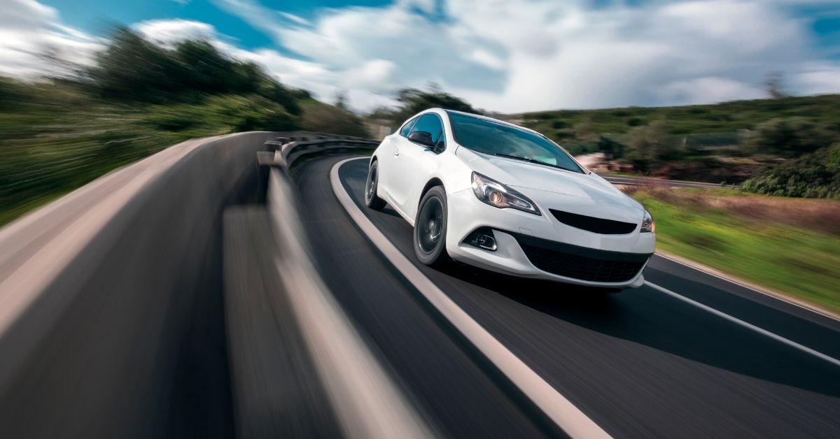 Have You Heard of Pay-Per-Mile Car Insurance - picture of white car driving with speed blur in foreground