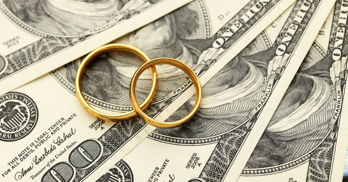 How to Deal When Your Wife Makes More - picture of wedding rings sitting on hundred dollar bills
