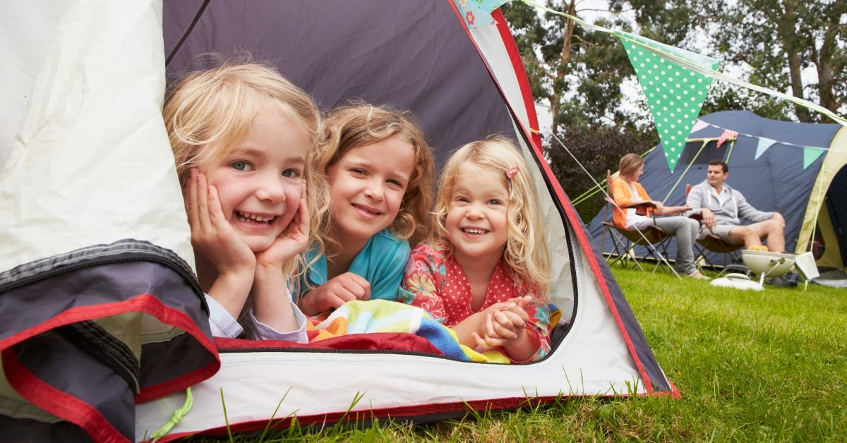 Ways to Save on Summer Activities for Kids - picture of young kids peeking out of a tent