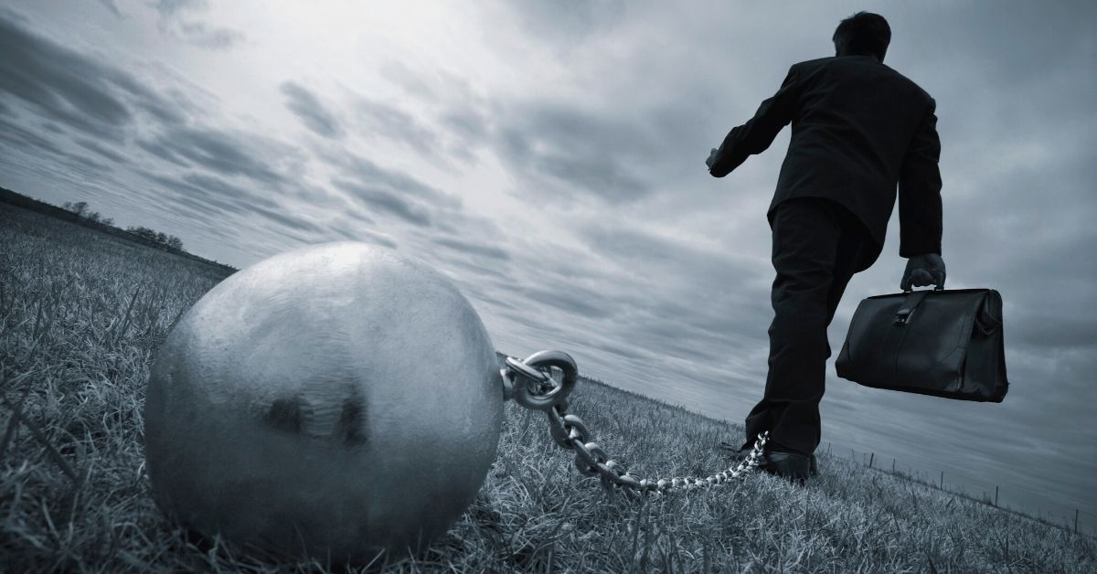 Ways to Slow Down Interest and Get Ahead Faster - picture of businessman walking away with ball and chain attached