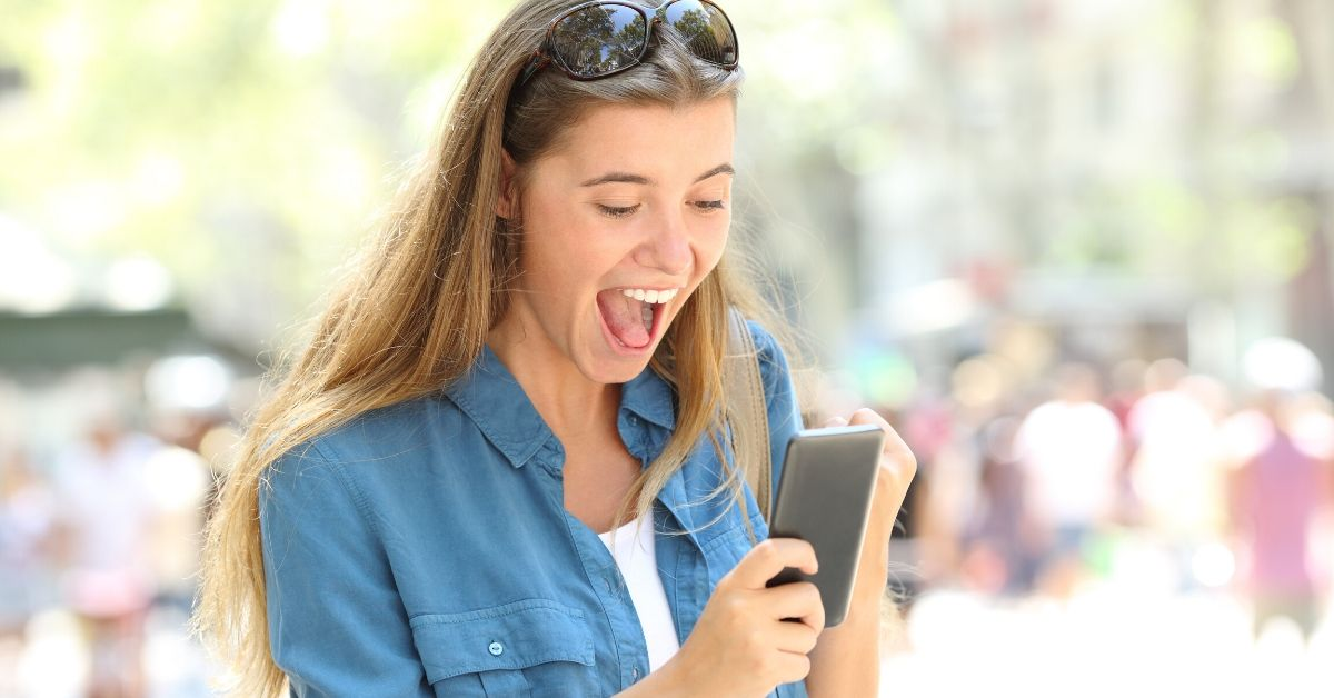 Republic Wireless Review - picture of young woman excitedly reading cell phone